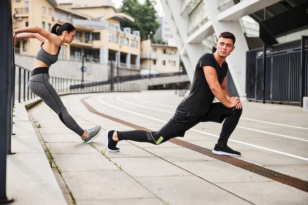 Atletische knappe man doet lunges en slanke vrouw doet triceps push-ups in stedelijke straat