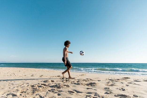 Atletische man bal schoppen op strand
