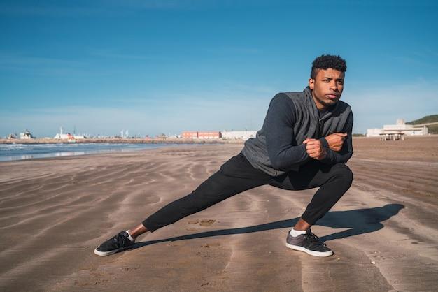 Atletische man benen strekken voor de training