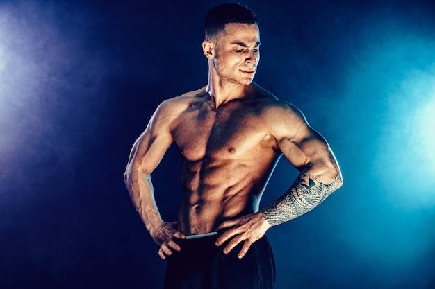 Atletische man buigen spieren in op donker met rook. sterke bodybuilder met perfecte buikspieren.