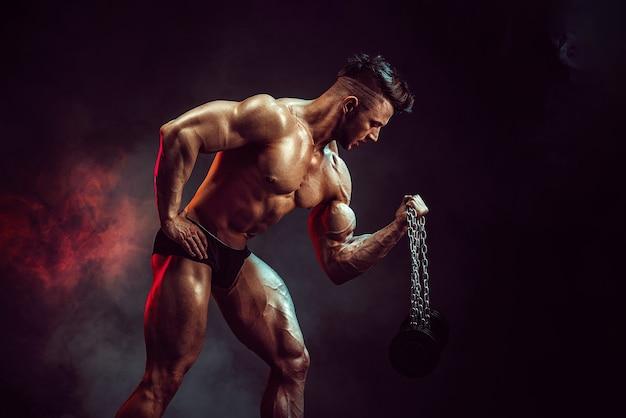 Atletische man buigen spieren in studio op donkere muur met rook. sterke bodybuilder met perfecte buikspieren.