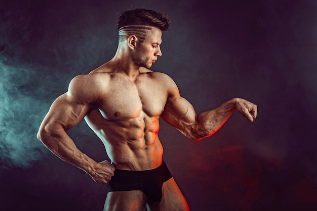 Atletische man buigen spieren met rook. sterke bodybuilder met perfecte buikspieren.