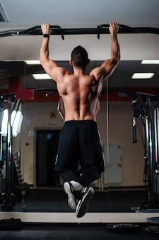 Atletische man die pull-up oefeningen op een dwarsbalk in de sportschool