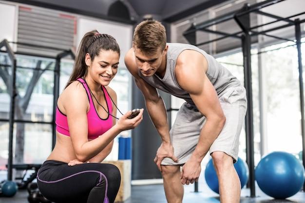 Atletische man die tijd controleert met trainervrouw bij gymnastiek