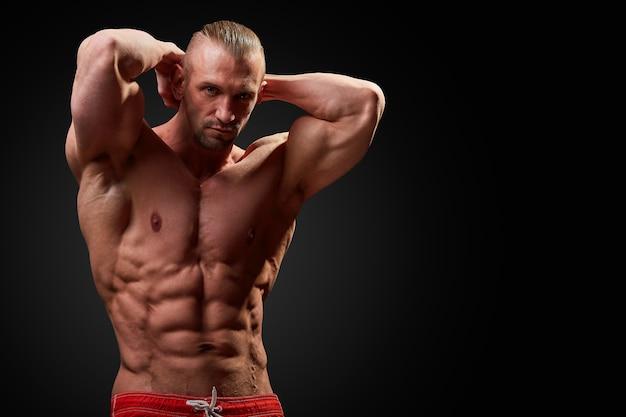 Atletische man die zich voordeed. foto van de mens met perfect lichaamsbouw op zwarte achtergrond. kracht en motivatie