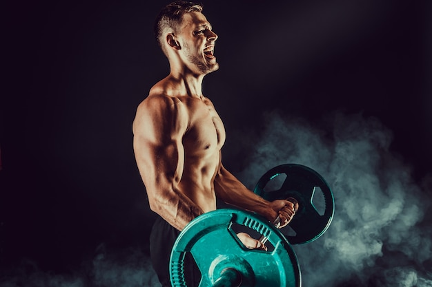 Atletische man doen oefeningen met halters op biceps. foto van sterk mannetje met naakt torso op donkere muur. kracht en motivatie.