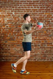 Atletische man doet evenwicht oefeningen met de bal