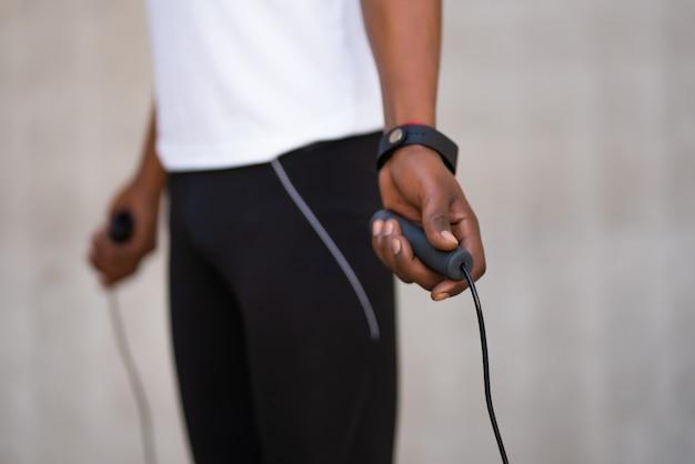 Atletische man doet oefening en springt het touw buitenshuis