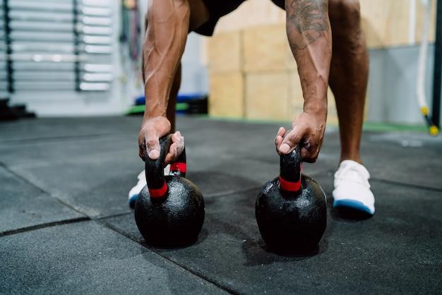 Atletische man doet oefening met crossfit kettlebel.