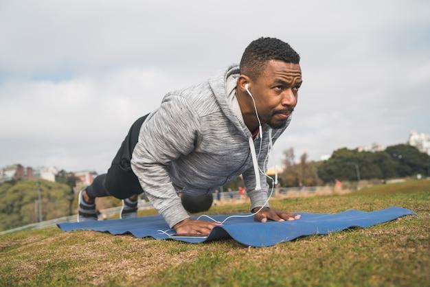Atletische man doet push ups.