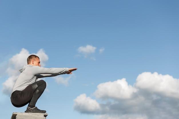 Atletische man doet squats met kopie ruimte