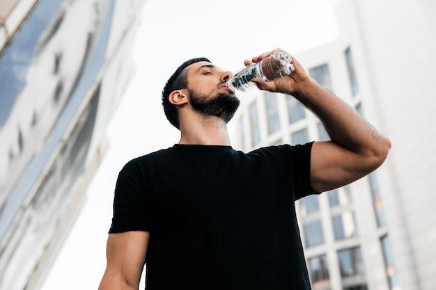 Atletische man drinkwater uit plastic fles na het joggen. sportieve mannelijke hardloper met donker kort haar. zwart t-shirt. wazig flatgebouwen op de achtergrond. lage hoek opname. drink meer water.