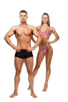 Atletische man en vrouw die de camera op een witte achtergrond bekijken