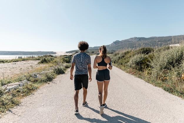 Atletische man en vrouw die langs weg lopen