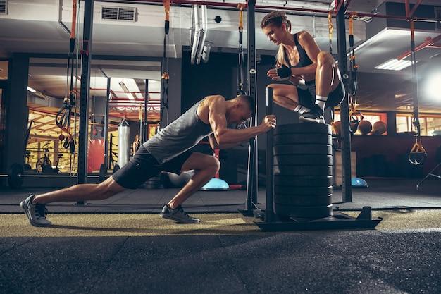 Atletische man en vrouw met domoren die en in gymnastiek opleiden oefenen.