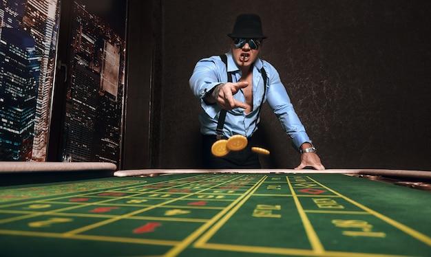 Atletische man gekleed in pak met een sigaar speelt in een casino