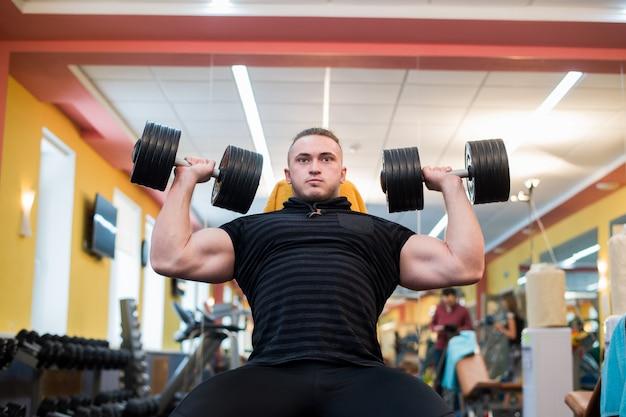 Atletische man houdt de halter boven het hoofd op de sportschool