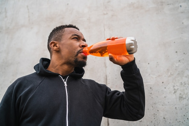 Atletische man iets drinken na de training.