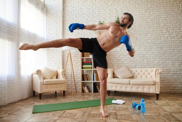 Atletische man in bokshandschoenen maakt kick.