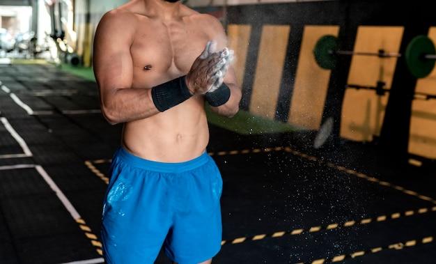 Atletische man in de sportschool met magnesium handen