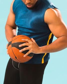 Atletische man in gym slijtage bedrijf basketbal