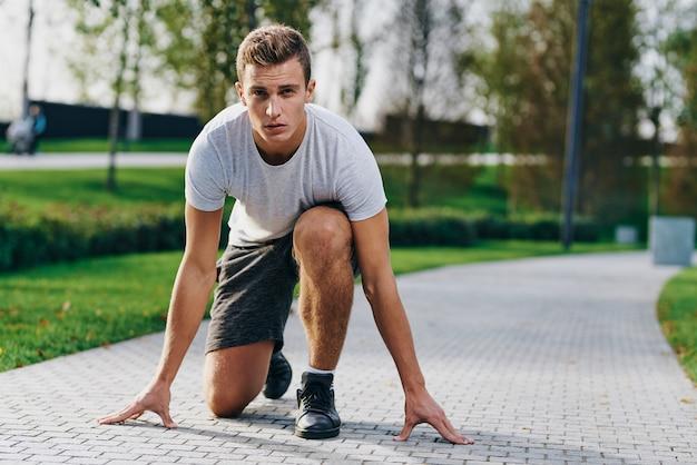 Atletische man in korte broek en een t-shirt bereidt zich voor op joggen in de natuur in het park in de buurt van de bomen op straat.
