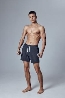 Atletische man in korte broek met halters in zijn handen pompte de motivatie voor lichaamsfitness op