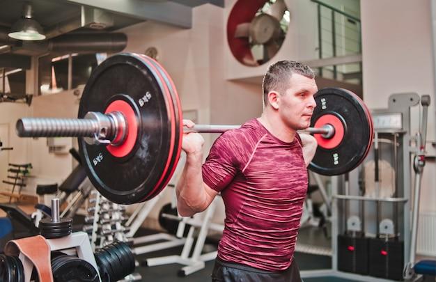 Atletische man in sportkleding doen oefening met zware halter op zijn schouders in de sportschool.