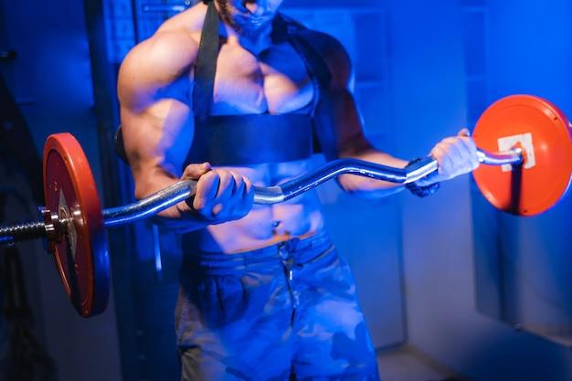 Atletische man in sportschool trainen met barbell. bodybuilder met perfect lichaam. blauwfilter. vooraanzicht. naakte torso.