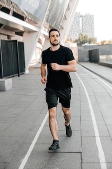 Atletische man joggen in de stad. gezonde levensstijl. man loopt. stedelijke stadslevensstijl. actief leven. buiten fitnessen. zwarte sportkleding. gelukkig mannelijke loper. grijze stad op de achtergrond.