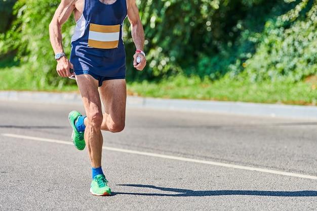 Atletische man joggen in sportkleding op weg van de stad