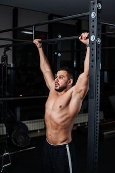 Atletische man maken pull-up oefeningen op een lat in de sportschool