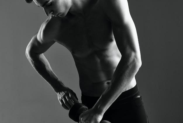 Atletische man met dumbbells in de hand die oefeningen doet