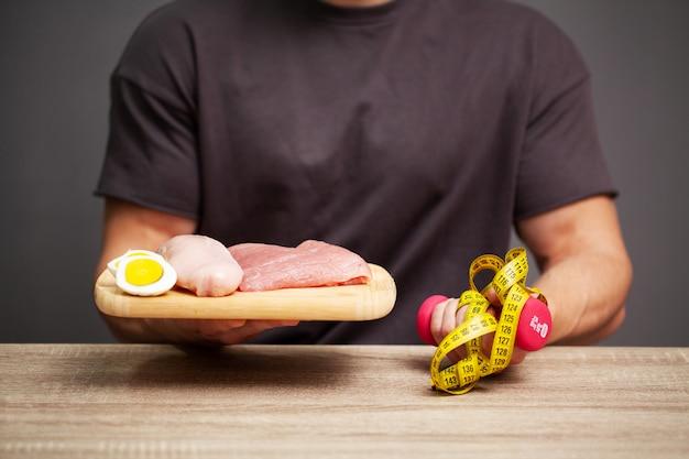 Atletische man met een bord met vlees voor de juiste voeding van de atleet