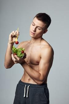 Atletische man met een gepompt lichaam plaat salade groenten gezonde voeding levensstijl. hoge kwaliteit foto