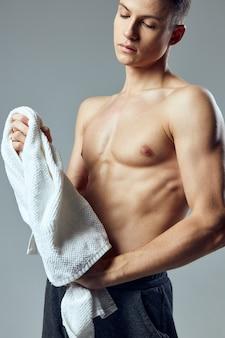 Atletische man met handdoek in handen opgepompt pers sportschool levensstijl