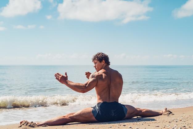 Atletische man met mooie spieren zit op een touw in de zomertraining aan de kust
