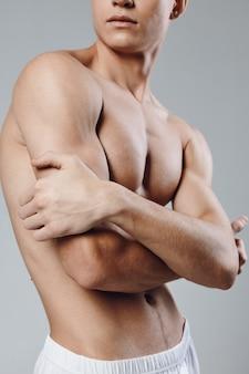 Atletische man met opgepompte armspieren die zichzelf knuffelen met zijn armen en naar de zijkant kijken.