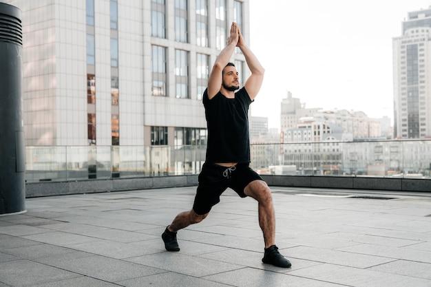 Atletische man oefent low lunge pose met opgeheven armen. jonge man in zwarte sport t-shirt en leggins die zich uitstrekken in yoga pose. stedelijk sportconcept. ochtend opwarmen.