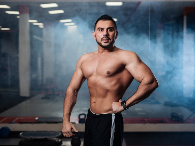 Atletische man poseren, pronken met zijn spieren in de sportschool