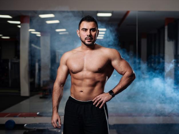Atletische man poseren, pronken zijn spieren in de sportschool