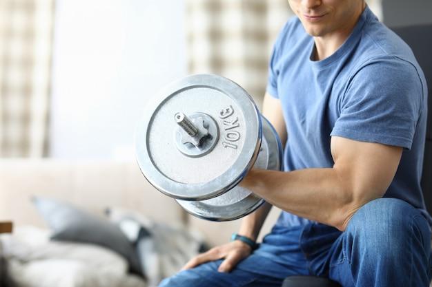 Atletische man schudt zijn biceps met halter in zijn handen