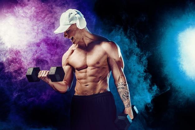 Atletische man training spieren met halters in op donker met rook. sterke bodybuilder met sixpack, perfecte buikspieren, schouders, biceps, triceps en borst poseren met koptelefoon.