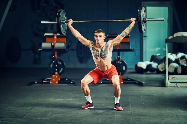 Atletische man traint in de sportschool met een barbell