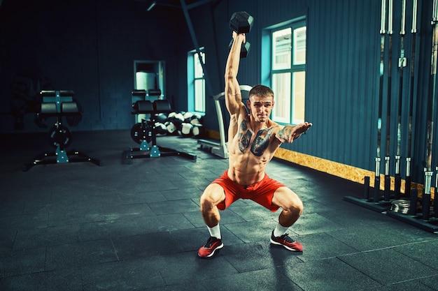 Atletische man traint in de sportschool met een halter
