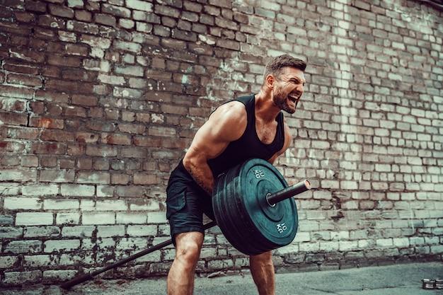 Atletische man uit te werken met een barbell. kracht en motivatie. oefening voor de spieren van de rug