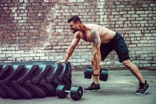 Atletische man uit te werken met een halter. kracht en motivatie. oefening voor de spieren van de rug