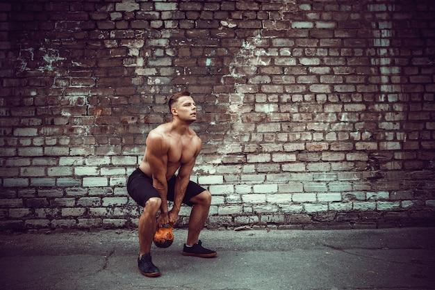 Atletische man uit te werken met een kettlebell. kracht en motivatie
