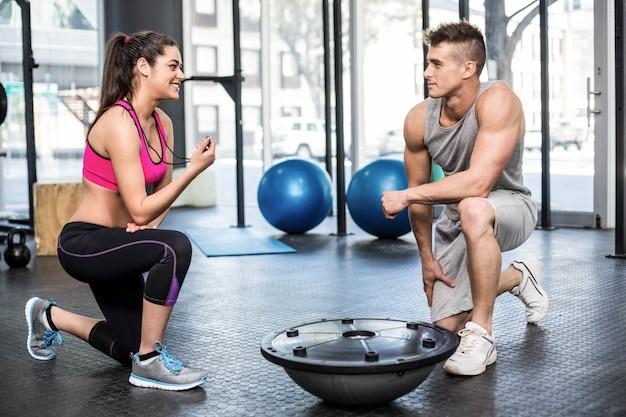 Atletische man uitwerken geholpen door trainer vrouw bij gymnastiek