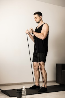 Atletische man voert oefeningen uit met behulp van een weerstandsband. welzijn en activiteit concept. sterke man die aan het oefenen is om een fit lichaam te hebben. hard trainingsconcept. man doet handoefeningen thuis.
